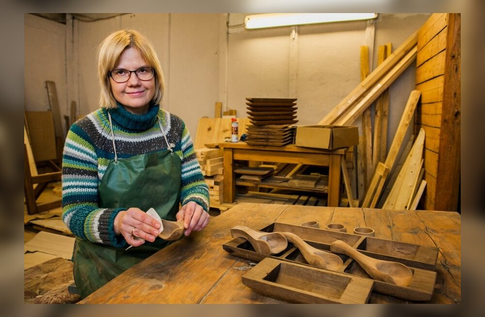 Naine teeb vanadest palkidest kappe, laudu ja puunõusid
