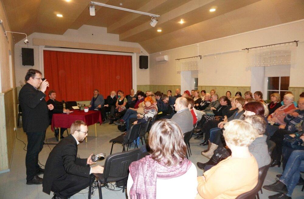 """Auditoorium Valdur Mikita loengul """"Ajakaevu kiigates"""" Valtu seltsimajas 21. novemberil 2016. Pildil vasakul kükitab Ööülikooli toimetaja Jaan Tootsen, tema kõrval, näpp püsti, seisab Vahur Tõnissoo ja laua taga istub kirjanik Valdur Mikita."""