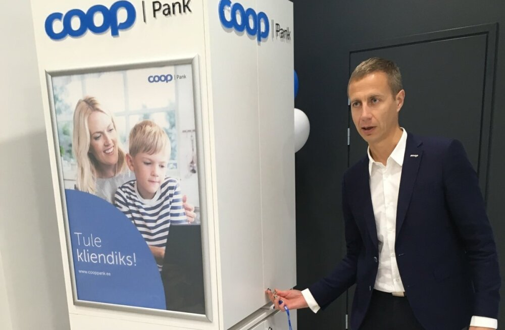 """Coop Panga juhatuse esimees Margus Rink näitab panga mobiilset """"kappi"""", mis viiakse 20 kauplusse üle Eesti ja mida saab vajadusel uutesse kohtadesse üles panna."""