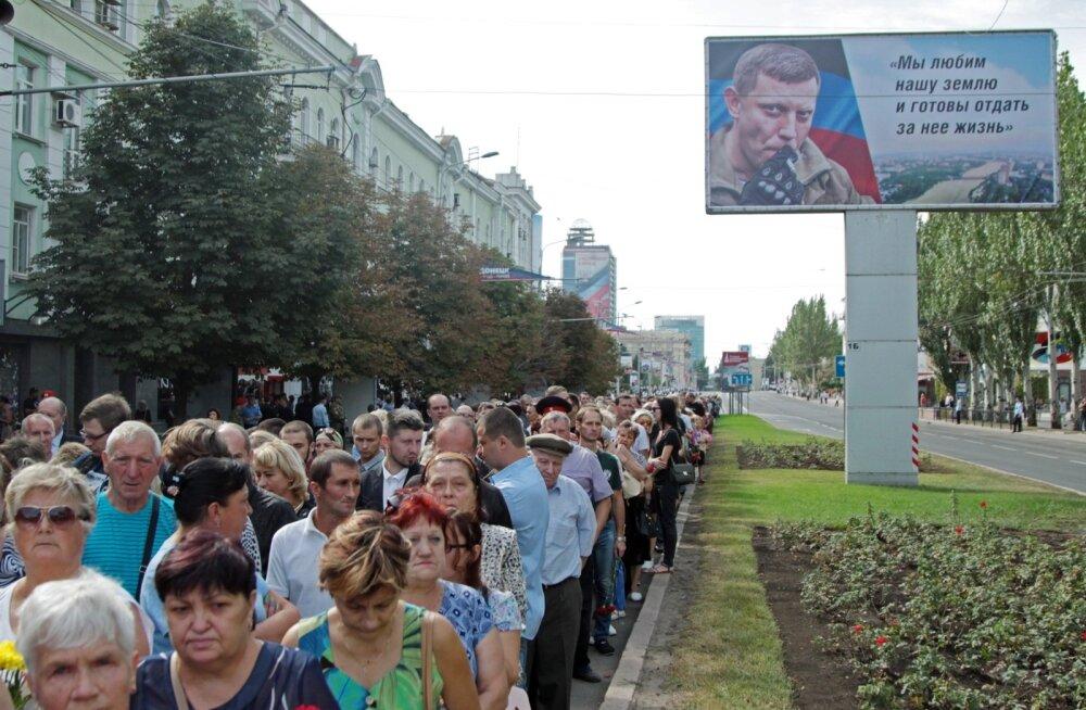 """Eile moodustasid Zahhartšenkole austust avaldajad Donetski linnas pika järjekorra. """"Me armastame oma maad ja oleme tema eest valmis oma elu andma,"""" kõlab üks Zahhartšenko mõttetera plakatil."""