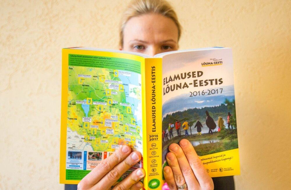 Tartumaa Arendusseltsi tegevjuht Kristiina Tammets näitab Lõuna-Eesti heade pakkumiste raamatut, kus on üle 300 soodustust võimaldava kupongi.